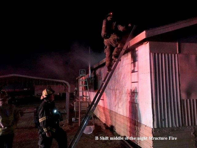 Firefighters in fire gear at night climbing a ladder to the top of a burning modular home