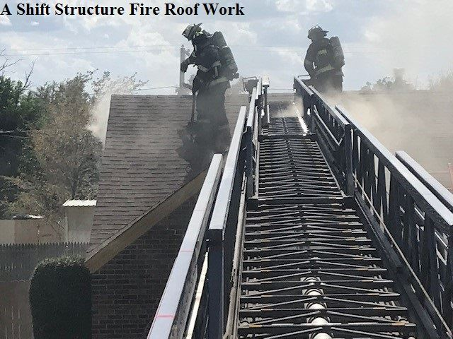 Firefighter working on the smoking roof of a house with a fire engine extending ladder arm nearby