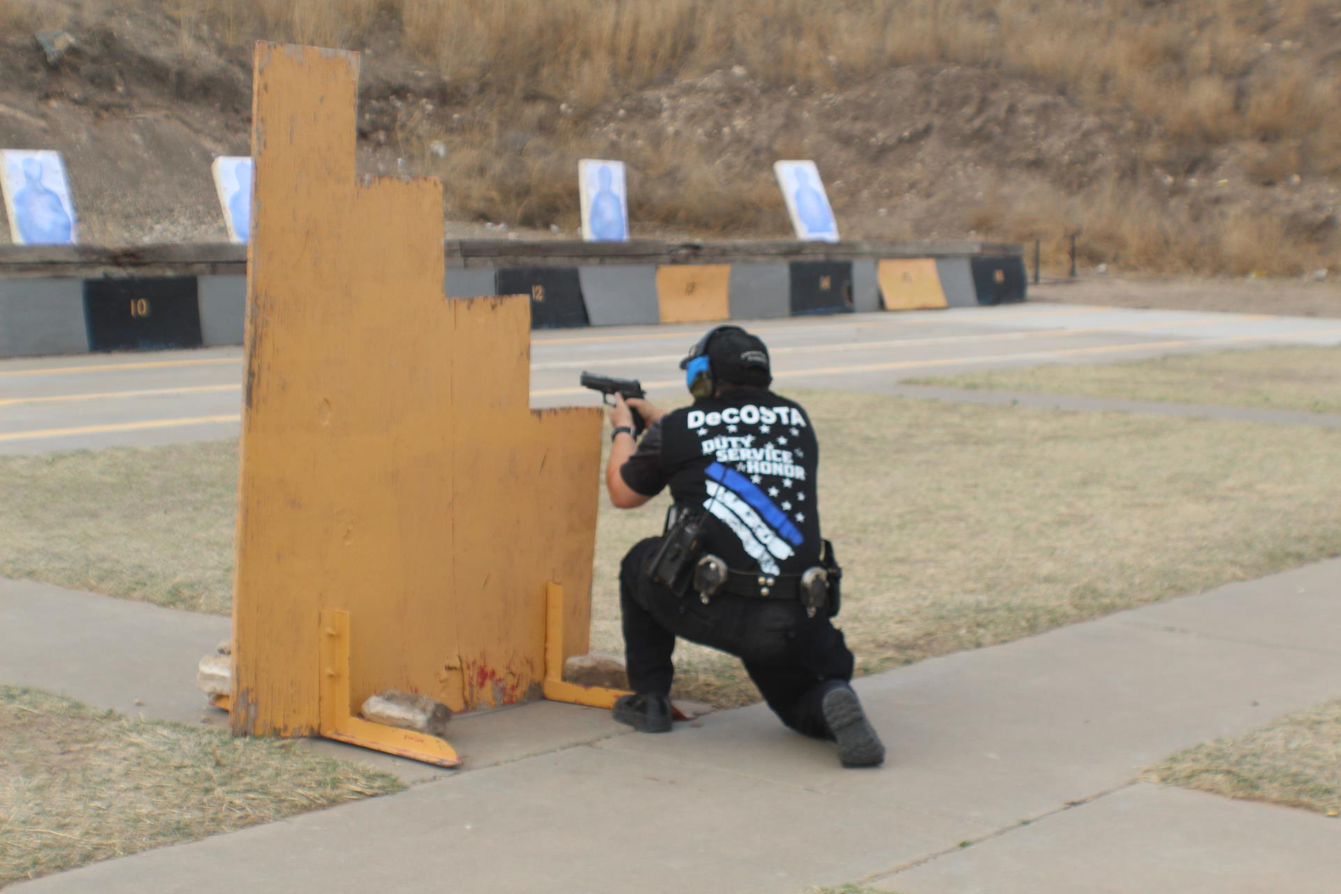 Recruit holding pistol, crouched behind a wooden barrier to aim at targets
